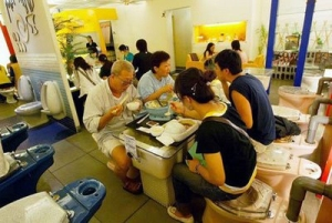 Customers sitting on toilets and eating on sinks